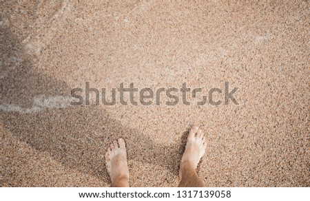 Barefoot male legs standing on coastal sand at sunny day, top view #1317139058