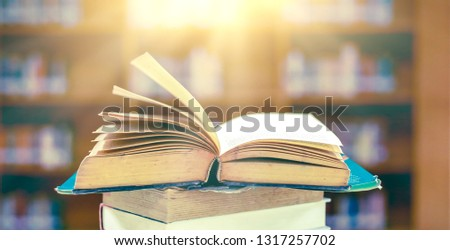 Stack of books in the library and blur bookshelf background #1317257702