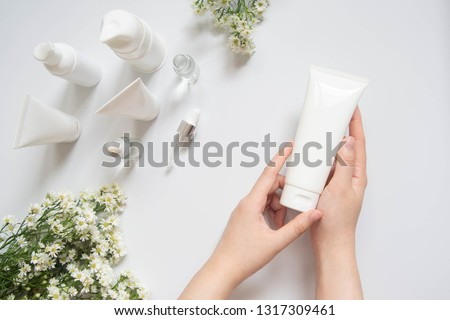Young female hand holding blank white squeeze bottle plastic tube w/ organic natural skincare products and flower on white table. Packaging of lotion, cream or serum. Beauty cosmetic skincare concept. #1317309461