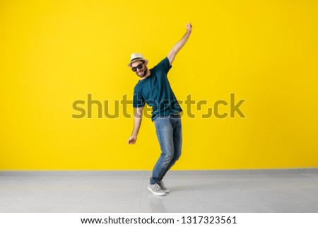 Handsome young man dancing near color wall #1317323561