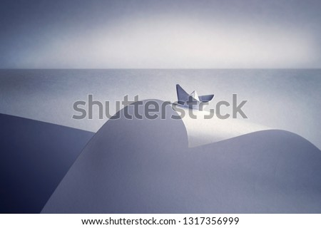 Paper ship on the crest of a paper wave
