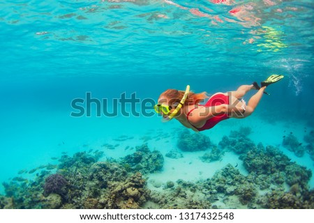 Young happy girl in snorkeling mask jump and dive underwater to see tropical fishes in coral reef sea pool. Travel activity, water sports, outdoor adventure, on family summer beach holiday with kids #1317432548