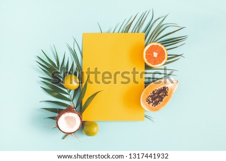 Summer composition. Tropical palm leaves, fruits, yellow paper blank on pastel blue background. Summer concept. Flat lay, top view, copy space