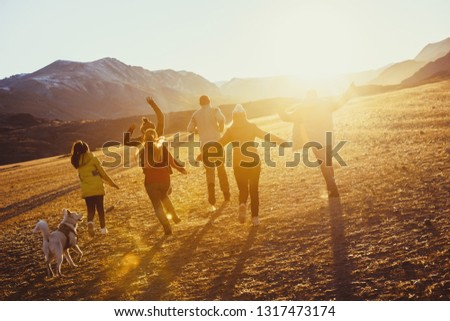 Big group of happy friends run and jump at sunset field against mountains and sun #1317473174