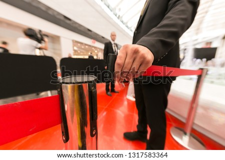 Security hand fastens a red tape closing the passage