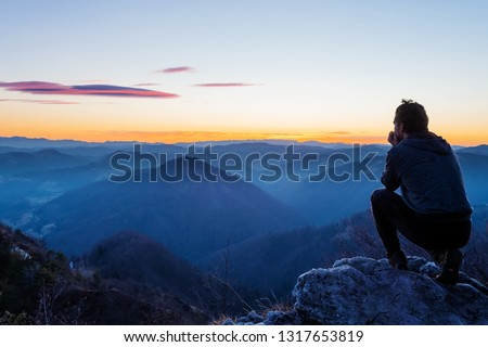 Male hiker crouching on top of the hill and enjoying scenic view of twilight landscape below. Hiking, achievement, expectation, optimism and self-reflection concepts. #1317653819