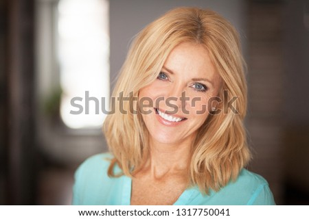 Middle aged woman smiling at the camera at home Royalty-Free Stock Photo #1317750041