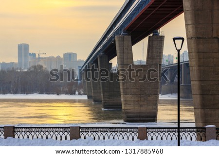 View of the Novosibirsk Metro Bridge across the Ob River. Siberia, Russia. The embankment is covered with snow. Cold weather. Beautiful sunlight reflected in the water. In the distance buildings. #1317885968