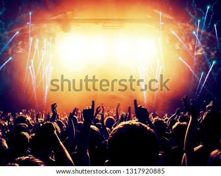 Concert spectators in front of a bright stage with live music, fireworks are visible in the air. #1317920885