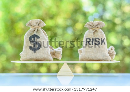 Risk assessment / risk analysis and management concept : Dollar and risk bags on basic balance scale, depict evaluation of financial risk that investor involved in stock, futures and derivative market #1317991247