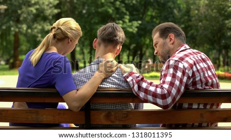 Caring mother and dad supporting sad teen son sitting on bench in park, crisis Royalty-Free Stock Photo #1318011395
