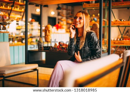Beautiful Blonde Woman Talking on Smartphone at Cafe #1318018985