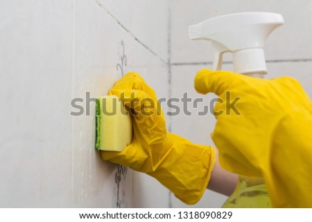 Cleaning the tile wall with a sponge and spray. #1318090829
