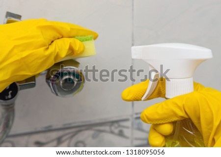Using a sponge and a detergent while cleaning sink and tap in bathroom. #1318095056