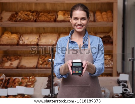 Seller holding payment terminal in bakery. Space for text