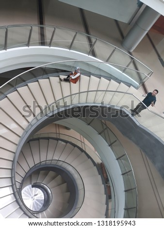 KUALA LUMPUR, MALAYSIA - FEBRUARY 20, 2019 : Visitor post for photograph at the spiral staircase inside the Bank Negara Malaysia Museum and Art Gallery in Kuala Lumpur, Malaysia. #1318195943