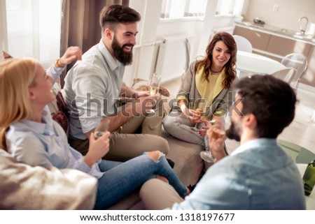 Group of happy friends sitting and drinking wine at home interior. #1318197677