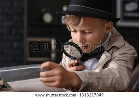 Cute little detective working with evidence at table Royalty-Free Stock Photo #1318217849