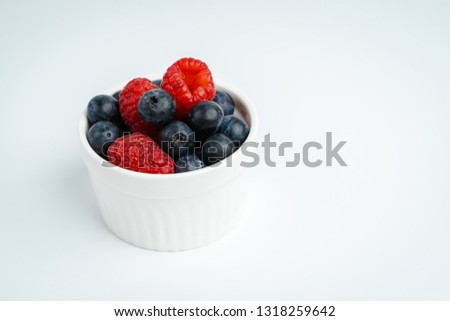 Fresh raspberries and blueberries in white bowl on wood board, Close up of ripe sweet berries on isolated background #1318259642