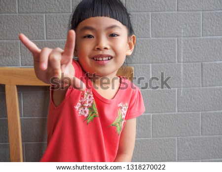 Little girl shows hand sign I love you. Cute hair style.