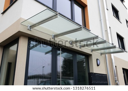 Front door canopy made of glass Royalty-Free Stock Photo #1318276511