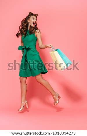 Full length portrait of a beautiful young pin-up girl wearing dress standing isolated over pink background, carrying shopping bags