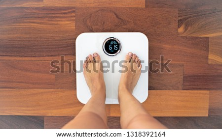 Woman bare feet standing on a digital scale with body fat analyzer that uses bioelectrical impedance (BIA) to gauge the amount of fat in your body #1318392164