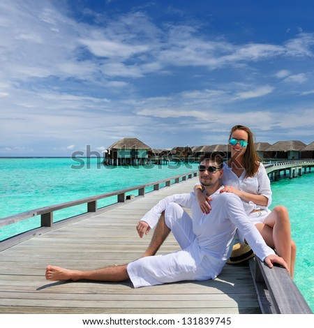 Couple on a tropical beach jetty at Maldives #131839745