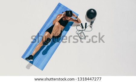 Top view of a female athlete doing abdomen exercises. Woman in fitness wear training doing abdomen crunches with a medicine ball and skipping rope by her side. #1318447277