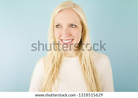 Young Woman smiling in studio with long blonde hair in front of a blue background #1318515629