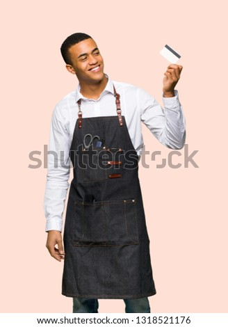 Young afro american barber man holding a credit card and thinking on isolated background