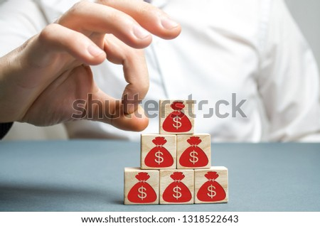Businessman removes a cube with a picture of dollars. Bankruptcy concept. Economic recession. Financial crisis. Capital outflow. Sabotage of the economy. Pressure on small businesses. Falling prices. #1318522643