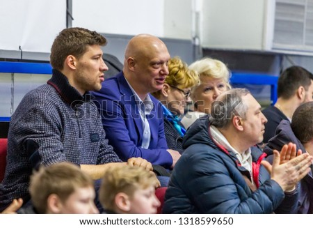 Odessa, Ukraine - Febr 16, 2019: Fans of basketball team and spectators in stands emotionally support their team during intense play. Fan club. Visitors fill stands of stadium. Fans celebrate success #1318599650