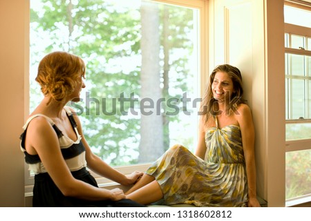 Two female friends chatting in a bay window of a log cabin.