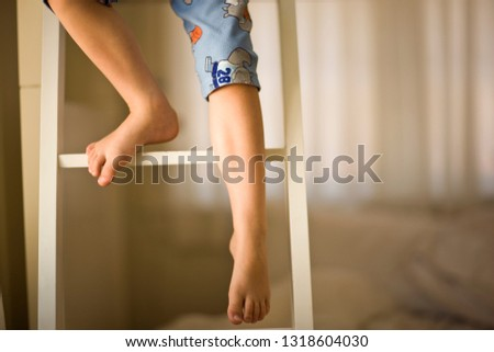 Boy climbing down the ladder of a bunk bed inside his bedroom.