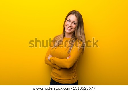 Young woman on yellow background keeping the arms crossed in frontal position #1318623677