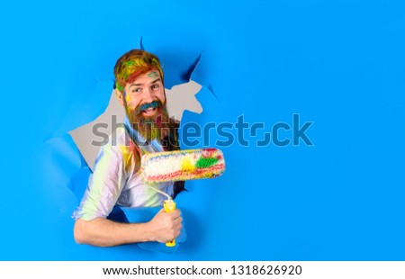 Repair. Professional painter in protective helmet making hole in paper wall. Happy painter man. Painter with painting roller through hole in paper. Handsome bearded worker with paint roller.Copy space #1318626920