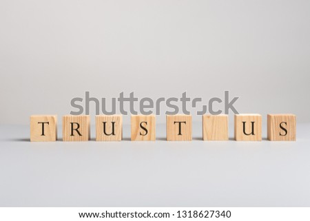 Wooden blocks placed in a row spelling trust us in a conceptual image of business support and customer service. #1318627340