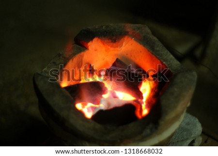 Heat from charcoal in the clay stove To provide warmth and use in cooking #1318668032