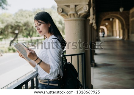 young elegant student woman reading textbook outside classroom at school studying. college girl standing indoor in hallway of old university building background in stanford. asian lady hard working. #1318669925