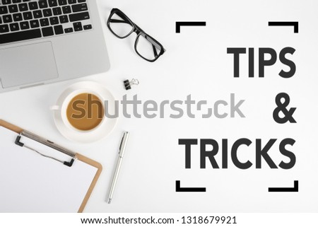 Tips And Tricks concept on desktop workspace with office supplies.