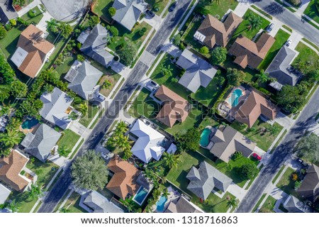 Aerial summer view of warm sunny neighborhood community roofs with diagonal streets and lots of houses with pools and palm trees.  Royalty-Free Stock Photo #1318716863
