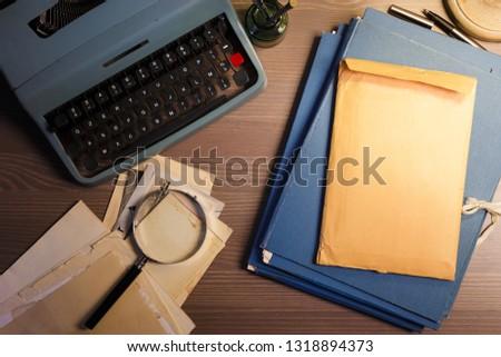 Investigator desk with confidential documents, magnifying glass, vintage typewriter. Secret documents investigation concept.  #1318894373