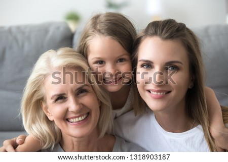 Head shot portrait of smiling grandmother, mother and daughter, looking at camera, excited granddaughter embracing mum and grandma, posing for family photo together at home, three generations #1318903187