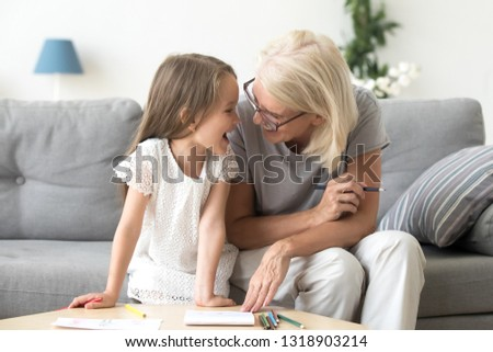 Happy grandchild with grandmother having fun, drawing colored pencils, sitting together on cozy sofa at home, laughing preschool girl with smiling grandma painting picture, playing with granddaughter