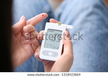 Diabetic woman using digital glucometer, closeup #1318923869