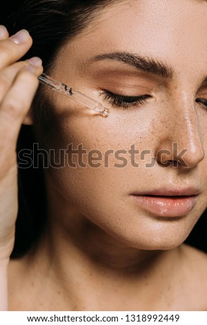 attractive young woman applying serum on face with pipette #1318992449