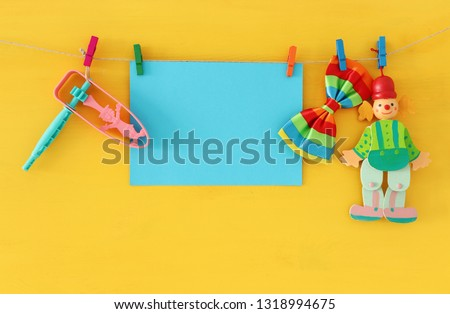 Purim celebration concept (jewish carnival holiday) with empty note for text, clown and noisemaker over wooden yellow background