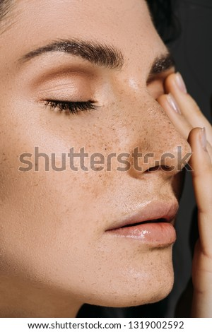 close up of beautiful tender woman with freckles on face isolated on grey #1319002592
