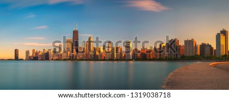 Chicago skyline panorama across Lake Michigan at sunset viewed from North Avenue Beach. Long exposure. #1319038718